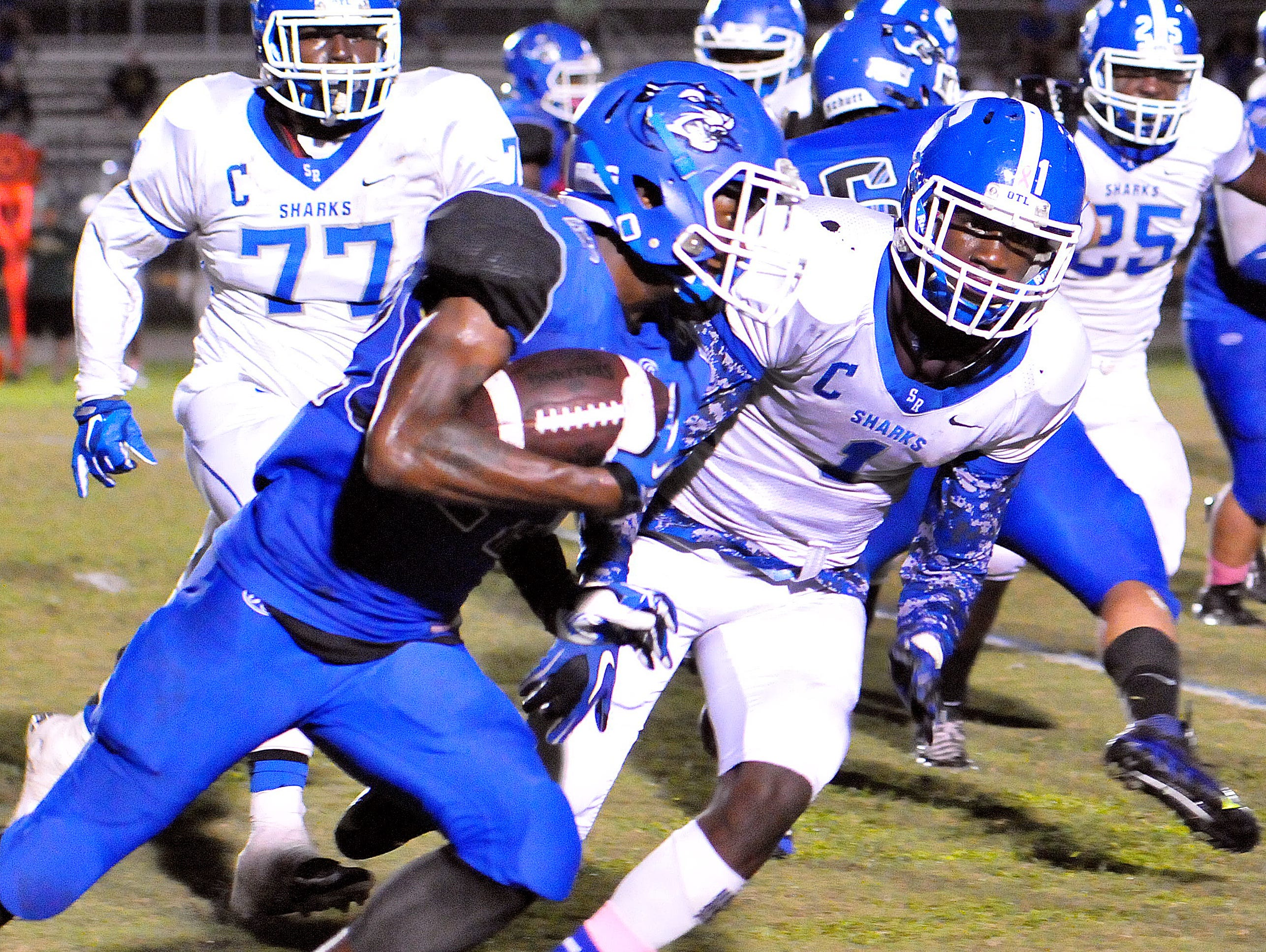 Heritage High's #22 Joshua Gaines turns the coner past a host of Sebastian Rivers High defenders for a nice gain on the play during Friday nights Homecoming game held Panthers stadium .