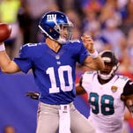 Eli Manning (10) of the Giants drops back to pass in the first quarter as Chris Smith (98) of the Jacksonville Jaguars defends during preseason action at MetLife Stadium on August 22, 2015 in East Rutherford, New Jersey.