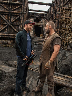 Director Darren Aronofsky, left, and actor Russell Crowe talk on the set of  'Noah,' as the Ark looms in the background.