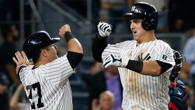 New York Yankees' Austin Romine, left, celebrates with the Yankees' Tyler Austin after scoring on Austin's seventh-inning, two-run, home run off Boston Red Sox starting pitcher David Price in a baseball game in New York, Tuesday, Sept. 27, 2016. The Yankees defeated the Red Sox 6-4.