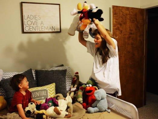 Hallie Perkins throws a handful of stuffed animals