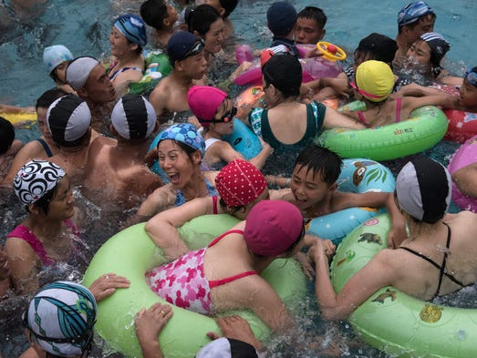 Swimmers gather in a wave pool at a water park in a