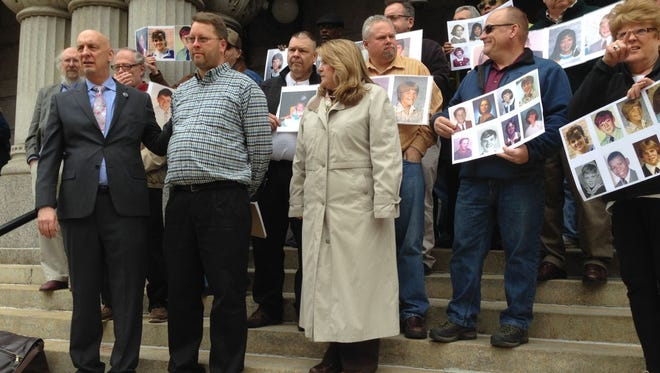 Peter Isley, front left, Charles Linneman, front middle, and Monica Barrett, front right, stand before a group of other clergy sexual abuse victims outside federal bankruptcy court in Milwaukee on April 17, 2014, in Milwaukee. Hundreds of sexual abuse victims have filed claims against the Archdiocese of Milwaukee in bankruptcy court.
