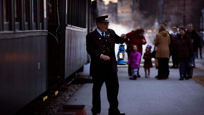 Conductor Brian Durham prepares to board the Maine Narrow Gauge Railroad's Polar Express train, Friday, Nov. 27, 2015, in Portland, Maine. The historic equipment, which operates on rails set two feet apart, was used from the 1870s until the 1940s.