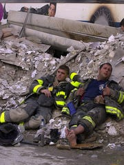 Two exhausted firefighters rest in the rubble at Ground Zero on Sept. 12, 2001.