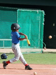 In this photo provided by the Guam Baseball Academy, a young baseball player works on hitting drills.