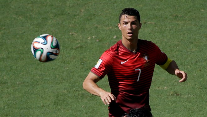 Portugal's Cristiano Ronaldo eyes the ball during the group G World Cup soccer match between Germany and Portugal at the Arena Fonte Nova in Salvador, Brazil, Monday, June 16, 2014. (AP Photo/Christophe Ena)