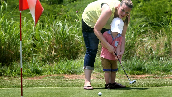 Lacey Garrett helps son Channing, 2, putt on Monday at the grand opening of Bloomfield Links Golf Course.