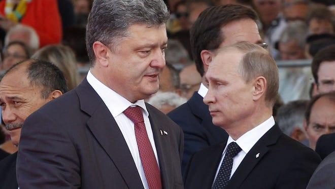 Ukraine's President-elect Petro Poroshenko (L) walks past Russian President Vladimir Putin in June during an  international D-Day commemoration ceremony.