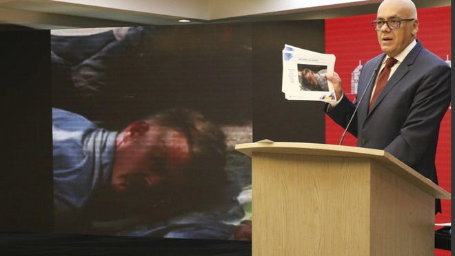 Venezuelan Communications Minister Jorge Rodriguez in May shows a photograph of a man he identified as former U.S. Special Forces soldier Luke Denman taken in Venezuela during the Texan's arrest.