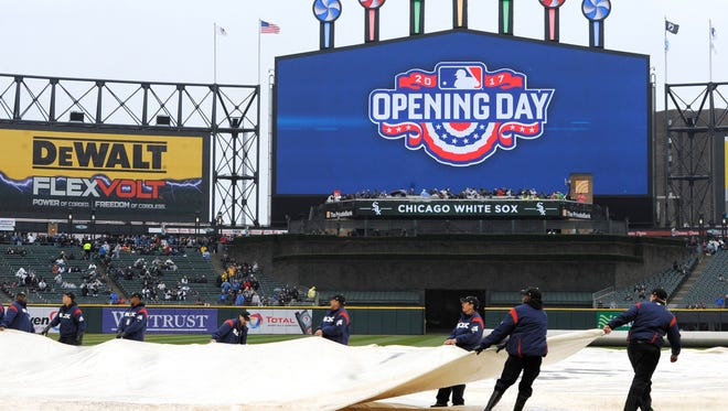The grounds crew puts a tarp on the field at Guaranteed Rate Field during a rain delay before the Chicago White Sox and Detroit Tigers game April 3, 2017, in Chicago.
