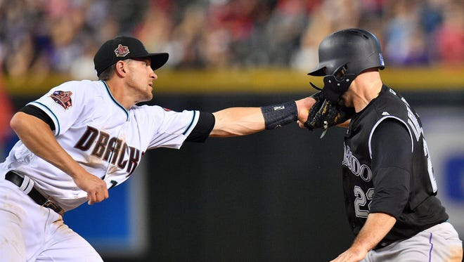 Mar 30, 2018; Phoenix, AZ, USA; Arizona Diamondbacks shortstop Nick Ahmed (13) tags out Colorado Rockies catcher Chris Iannetta (22) during the sixth inning at Chase Field. Mandatory Credit: Joe Camporeale-USA TODAY Sports