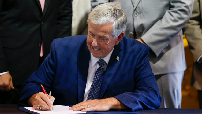 Missouri Gov. Mike Parson signs a bill at Hartman & Company on July 12, 2018. Parson signed off on the fiscal year 2022 budget this week, approving increases to education and health care and programs bolstered by federal stimulus funds.