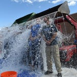 The Poudfre High School administration team gets dumped with ice water at the school Friday morning Aug. 29, 2014, for the ALS ice bucket challenge after being challenged by the administration at Rocky Mountain High School. In line with their agriculture heritage, they brought in two front end loaders to dump the ice water. Proceeds will be split between ALS and Spinal Muscular Atrophy.