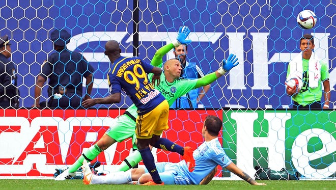 New York Red Bulls forward Bradley Wright-Phillips (99) scores a goal past New York City FC goalkeeper Josh Saunders (12) during the second half of a soccer game at Yankee Stadium. The New York Red Bulls defeated the New York City FC 3 - 1.