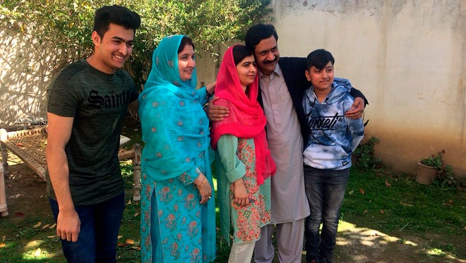 Pakistan's Nobel Peace Prize winner Malala Yousafzai, center, poses for a photograph with her family during a visit to her home in  Mingora, the main town of Pakistan Swat Valley, on March 31, 2018.