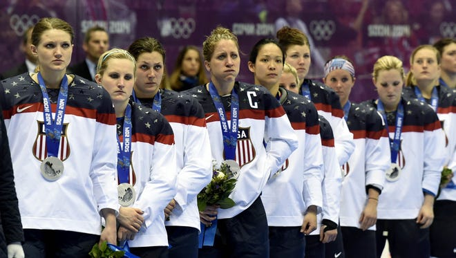 Members of the U.S. women's hockey team receive the silver medal at the 2014 Olympics.
