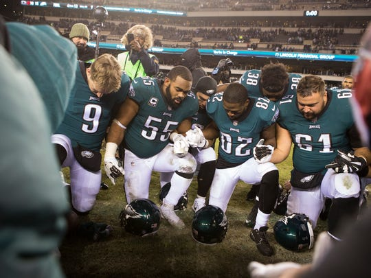 The Eagles' Nick Foles, 9, Brandon Graham, 55, Torrey Smith, 82, Stefen Wisniewski, 61, pray after defeating the Falcons in playoffs.
