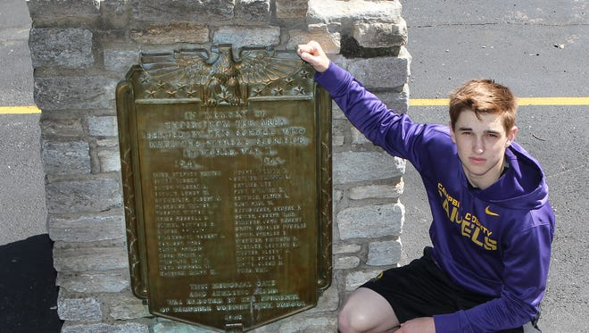 Noah Sell, a Campbell County High School student, with a Bronze plaque commemorating Campbell County men killed in World War II.