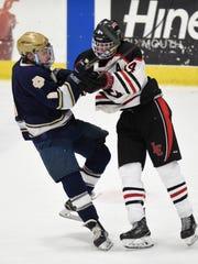 Livonia Churchill's Seth Kucharczyk (14) puts a hit