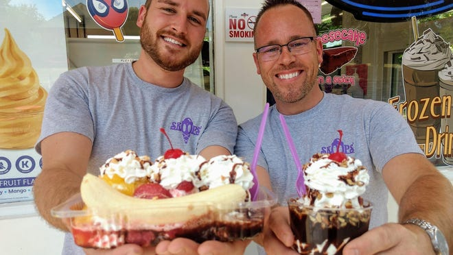 David Heldland (left) and Terry Rastetter, owners of Skoops in Barberton, with a banana split and hot fudge pecan sundae. They removed their masks and gloves for the photo.