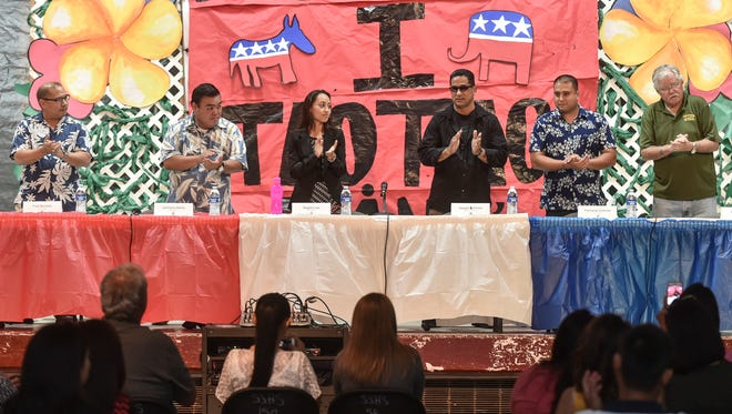 From left, new senatorial candidates Fred Bordallo, Jermaine Alerta, Regine Lee, Yigo mayoral candidate Joseph Flores, and senatorial candidates Fernando Esteves and Barry Mead, applaud the opening of a candidate forum at Simon Sanchez High School on April 27.