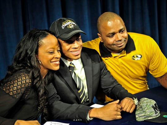 Emanuel Hall, center, poses for a photograph with his parents Daton Hall, right, and Shannon Simmons during the National Signing Day event at Centennial High School in Franklin, Tenn., Wednesday, Feb. 4, 2015.