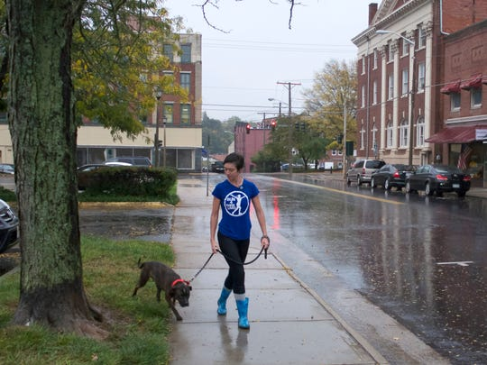 """It's part of life, Michelle DuVal of Staunton says about the rain October 15, 2014. She is walking her dog Roscoe, which she has had for just four days along Central Avenue in Staunton."