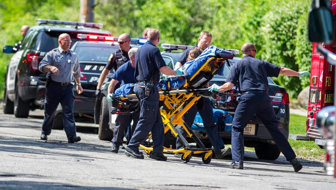 Rescue workers take a stabbing victim to the ambulance in Waukesha, Wis.