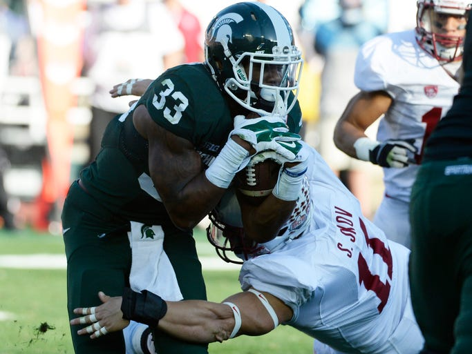 Stanford Cardinal linebacker Shayne Skov tackles Michigan State Spartans running back Jeremy Langford during the first half.