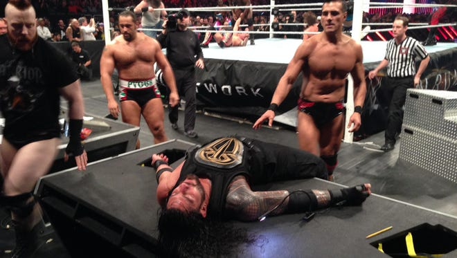 Roman Reigns lays helplessly on the Spanish announce table as Sheamus, left, Rusev and Alberto del Rio prepare to drive him through the table.