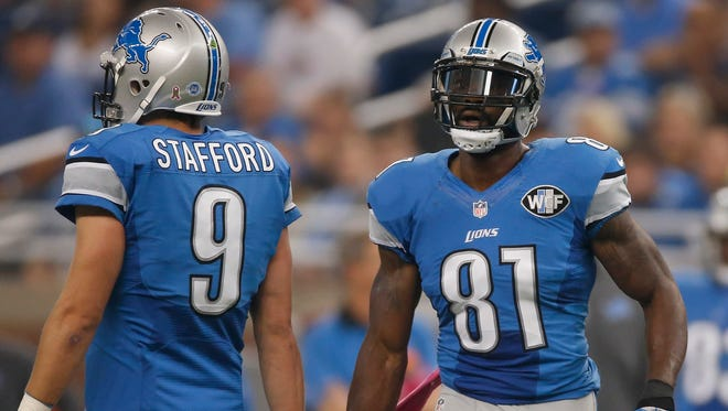 Lions WR Calvin Johnson celebrates breaking the franchise record of the most catches with Matthew Stafford while playing the Cardinals at Ford Field on Oct. 11.