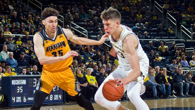 Michigan's Moritz Wagner drives on Kennesaw State's Zach Cameron during the first half.