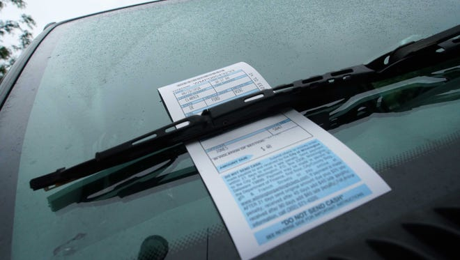 A vehicle along Market Street sits with a City of Wilmington parking ticket under the windshield wiper.