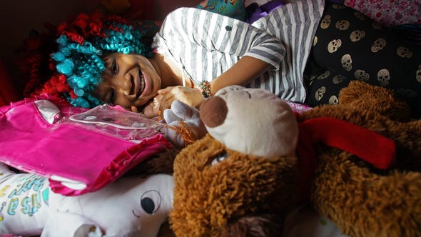13 year-old Trinity Neal lays amongst her many plush