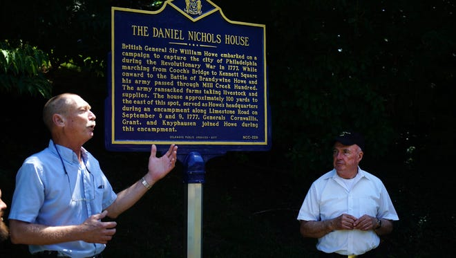 Walt Chiquoine, with the Hockesin Historical society, reads the words on an historic marker that was unveiled marking the spot where the British army camped in Hockessin in the days before the Battle of Brandywine. The plaque rest on the side of Limestone Road near the Hockessin Greene development. Joe Lake stands alongside.