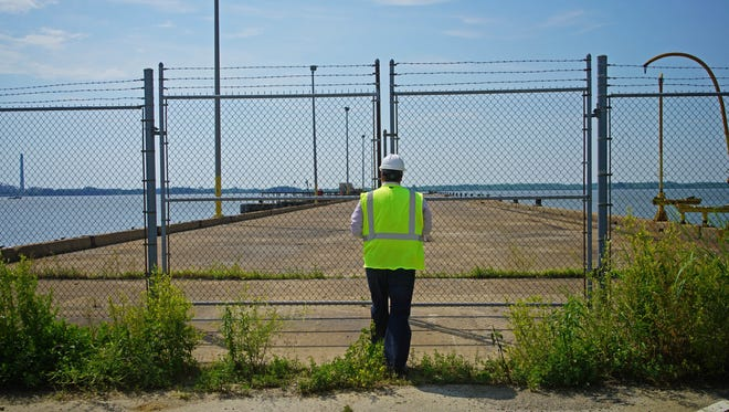 Keith Delaney, the principal partner of the Pennsylvania-based real estate investment firm D2 Management, opens up the gates to pier at the former General Chemical Corp. site along the Delaware River. Delaney and his business partners say they will bring new heavy industrial development to the property, thanks to a recent change in Delaware's Coastal Zone Act.