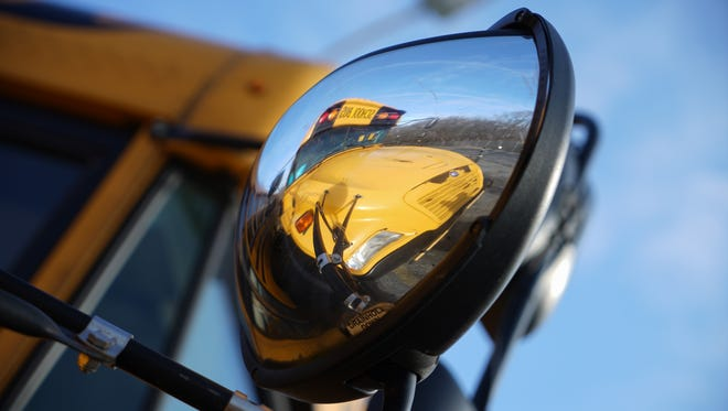 Colonial School District reflects in a rearview mirror of a bus in the district's bus yard.