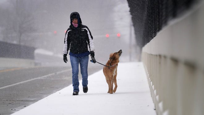 Dawn Smith walks her dog Maui across the Augustine Cutt Off Bridge as snow begins to fall from a passing nor'easter.