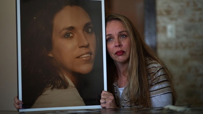 Crystal Waddell, of Northeast, Md., holds a picture of her 38 year-old sister Tammy who died last month of a heroin overdose. Her family is trying to finds out the content of the heroin that killed her and where it came from.