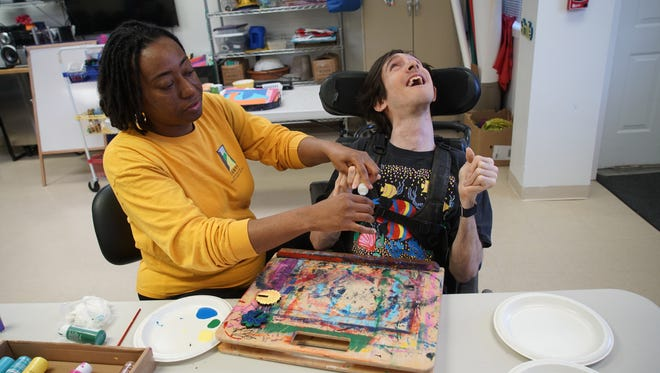 Sharuanda Robinson, a program associate at C.E.R.T.S., Inc., Adult Action Center in Newark, helps participant Alvin Neal create a decorative piece of art for the center's garden.