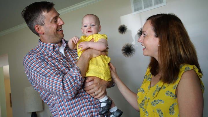 Kirk and Sally Lawrence play with their daughter who