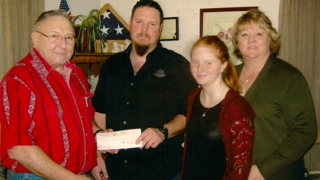 Knights of Columbus member Don Osmunson presents a check to, from left, Don, Emily and Lynn Ross.