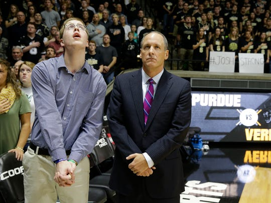 Josh Speidel, left, stands with Vermont head coach John Becker during the national anthem before an NCAA college basketball game against Purdue in West Lafayette, Ind., Sunday, Nov. 15, 2015. Speidel is recovering from a Feb. 1 auto accident that resulted in a traumatic brain injury.  (AP Photo/Michael Conroy)