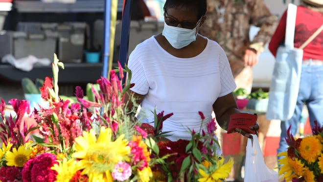 Charlie Cole shops at one of the vendor booths at the Fort Smith Farmers Market on Saturday on Garrison Avenue.
