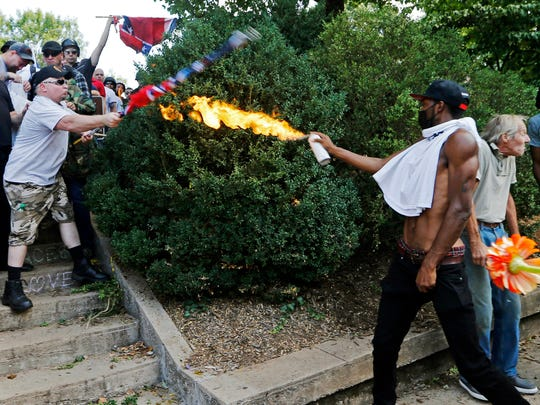 A counter demonstrator uses a lighted spray can Aug. 12, 2017, against a white nationalist demonstrator at the entrance to Lee Park in Charlottesville, Va