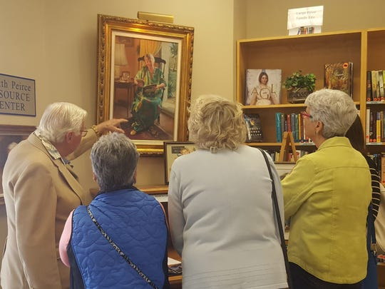 Bob Berran, left, discusses his painting to a group of guests at the First Anniversary Art Show at the Galleries at First Pres in Vero Beach.