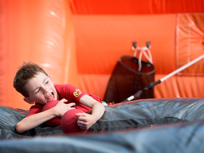 A young visitor plays on the inflatable during the
