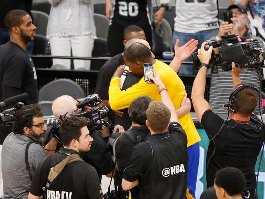 Golden State Warriors small forward Kevin Durant (right) hugs San Antonio Spurs shooting guard Manu Ginobili (left) after game four of the Western conference finals of the NBA Playoffs at AT&T Center.