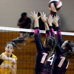 Merritt Island's Lexy Denaburg (6) spikes past the block of Palm Bay's Cierra Farnschlader (14) and Taylor Stanley (11) Wednesday's match.